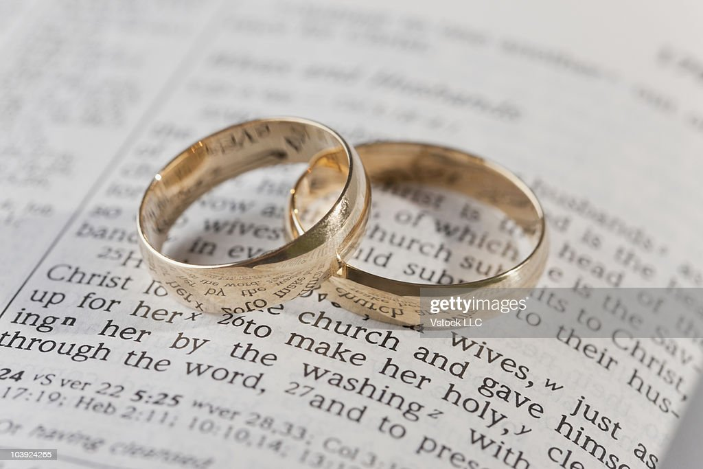 wedding rings on top of an open bible stock photo getty