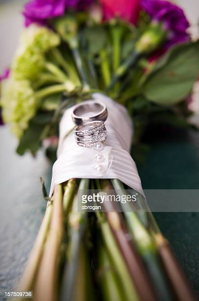 Wedding rings placed delicately on a bouquet of roses