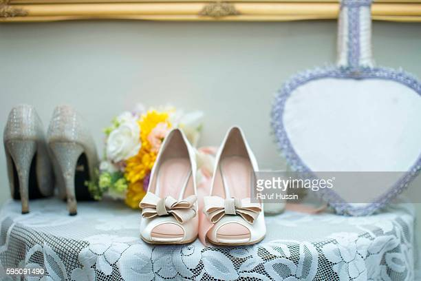 wedding shoes and wedding bouquet on the desk