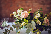Wedding table decorated with flowers, greenery style, closeup photo, warm toning.