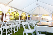 A group of chairs and tables under a white tent. Taken at a wedding before guests arrive.