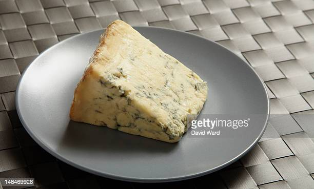 A wedge of blue cheese on a grey plate