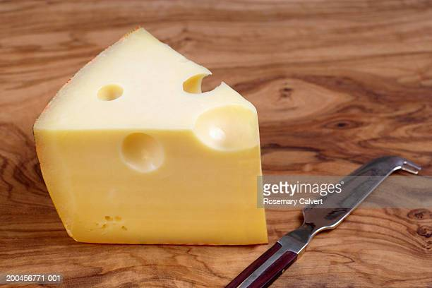 Wedge of gruyere cheese on board, with knife, close-up