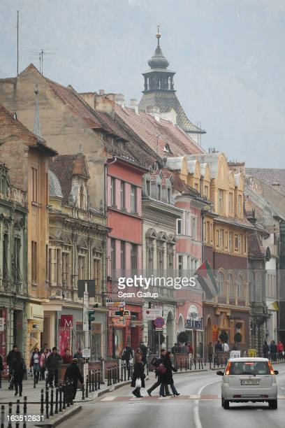 Weekend visitors walk among Saxonbuilt houses in the historic district on March 9 2013 in Brasov Romania Brasov in German called Kronstadt was...