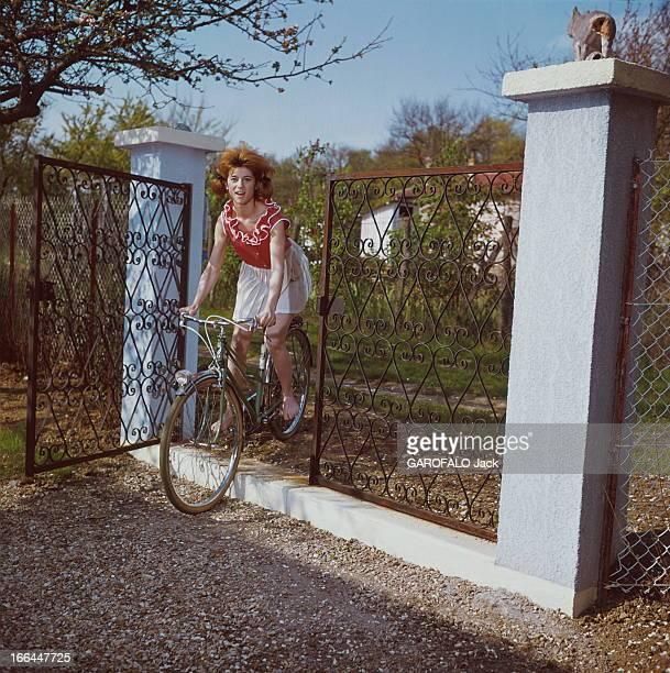 A Weekend With Sheila Attitude souriante de SHEILA 16 ans et demi faisant du vélo pieds nus passant la grille d'entrée de sa maison de BRUNOY