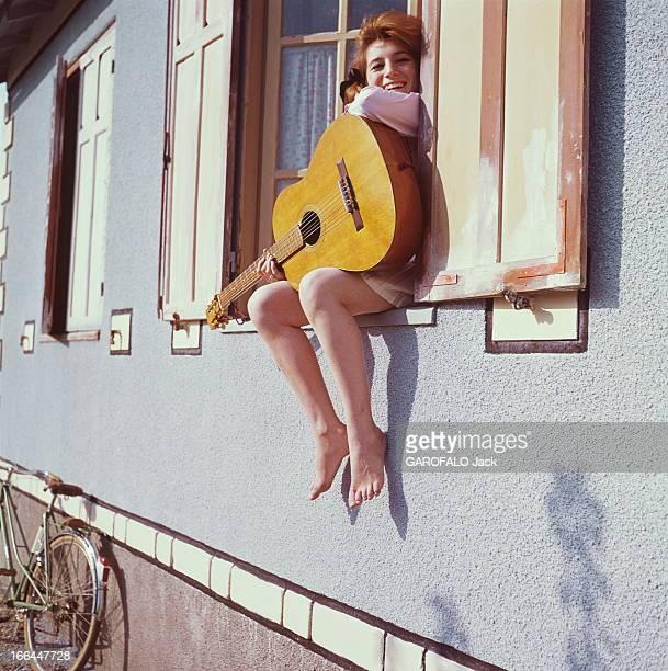 A Weekend With Sheila Attitude souriante de SHEILA 16 ans et demi posant assise sur le rebord de la fenêtre dans sa maison de BRUNOY une guitare dans...