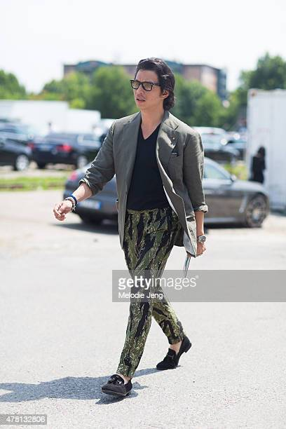 Wei Koh of The Rake enters the Gucci show in a Rubinacci jacket Dolce Gabbana shirt Cifonelli bespoke camouflage trousers and Tods shoes on June 22...