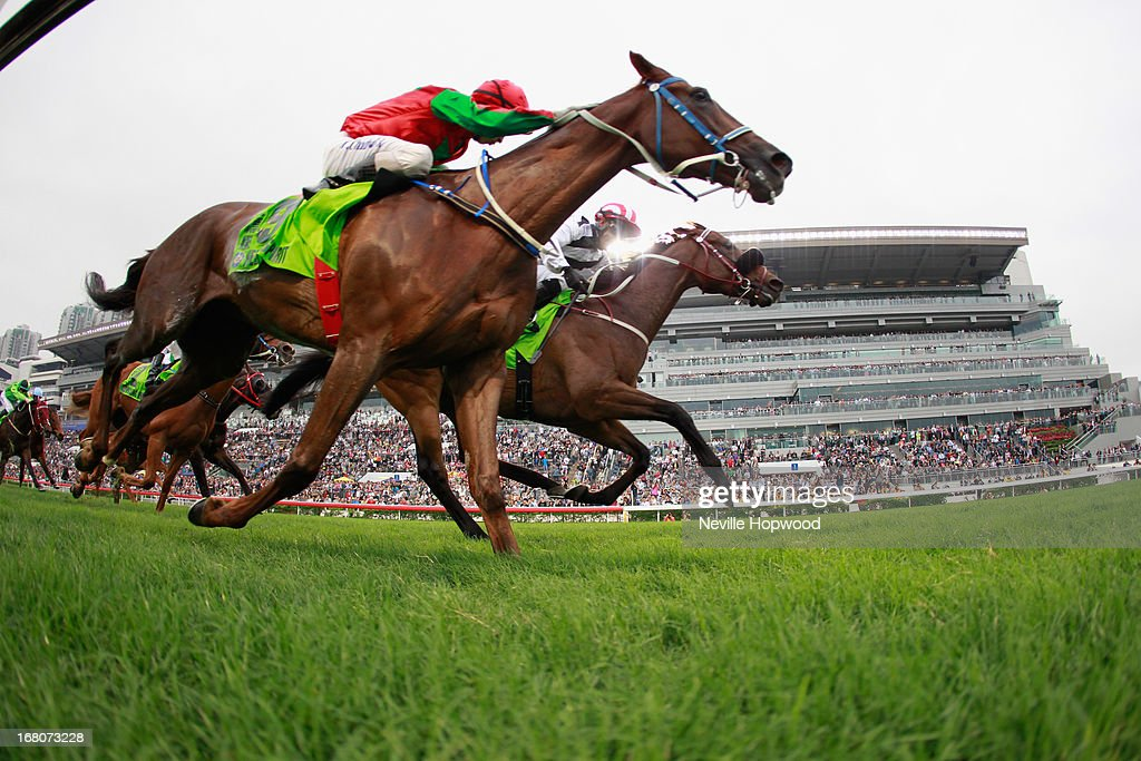 Weichong Marwing rides Dan Excel (red and white striped cap) from Matthew Chadwick on Helene Spirit to win the Group 1 The Champions Mile during The Champions Mile meeting at Sha Tin racecourse on May 5, 2013, in Hong Kong, Hong Kong.