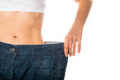 Slim stomach of young woman, thin body with perfect waist, showing her jeans after successful diet or sport training on isolated background. Weight loss and slimming