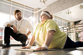 Portrait of obese young woman stretching during workout with fitness instructor in sunlight