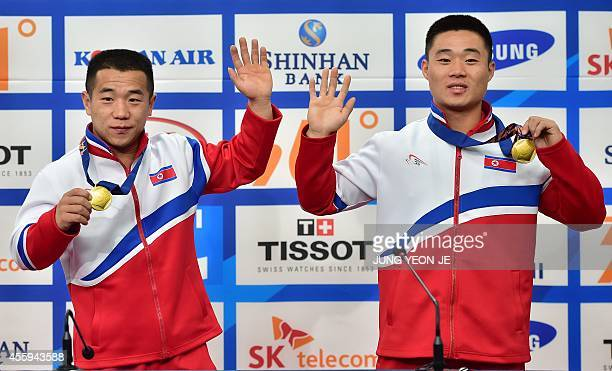 Weightlifting gold medallists North Korea's Om YunChol and Kim UnGuk pose at a press conference during the 2014 Asian Games at the main press center...