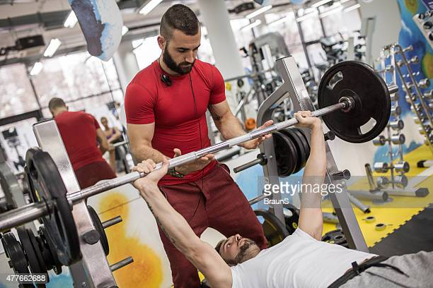 Weightlifting training with fitness instructor in a gym.