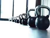 Shot of a bunch of kettle bells lined up in a row on the floor of a gym