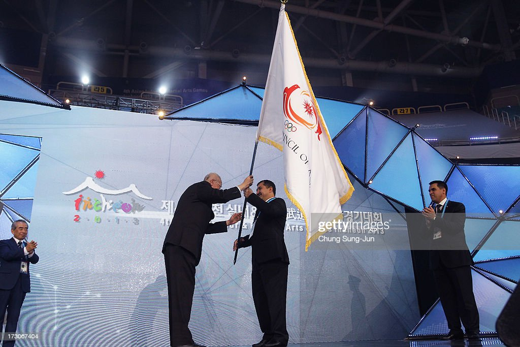Weiji Zhong (L), honorary vice President of OCA hand over OCA flag to Orazov Batyr (R),Sports Minister of Turkmenistan during closing ceremony of the 4th Asian Indoor & Martial Arts Games at Samsan World Gymnasium on July 6, 2013 in Incheon, South Korea.