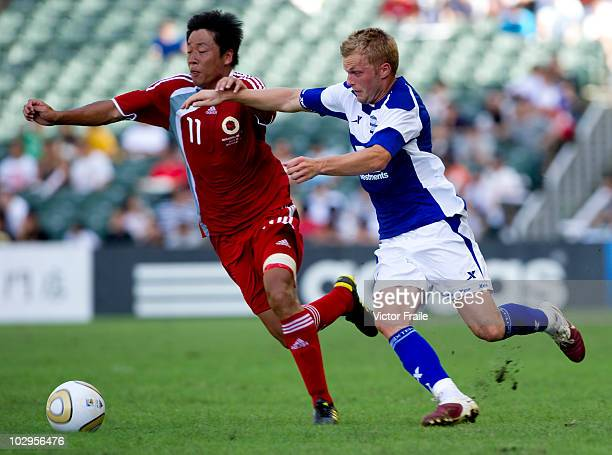Weijun Fan of Hong Kong League XI and Sebastian Larsson of Birmingham City compete for the ball during the Xtep Cup as part of Birmingham City's...