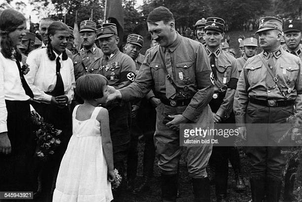 Weimar Republic Harzburg Front Meeting of right wing 'national opposition' in Bad Harzburg A little girl presting Adolf Hitler a flower bouquet left...