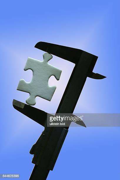 Weisses Puzzleteil wird mit einer Schublehre vermessen