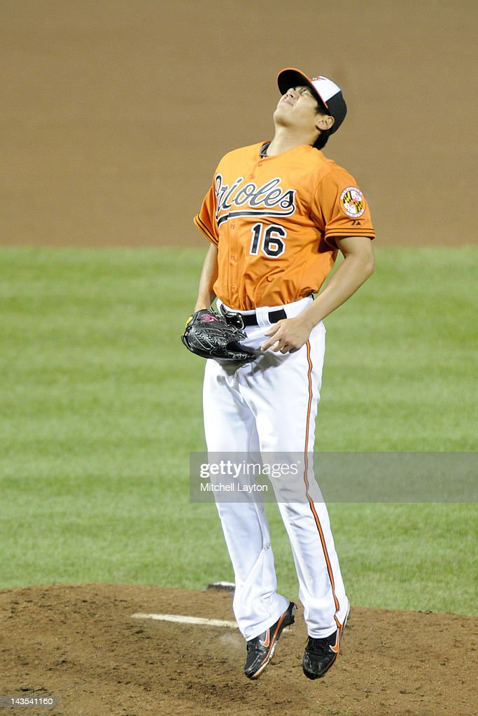 Wei-Yin Chen #16 of the Baltimore Orioles reacts after fielding a ground ball during the forth inning of a baseball game against the Oakland Athletics at Oriole Park at Camden Yards on April 28, 2012 in Baltimore, Maryland.