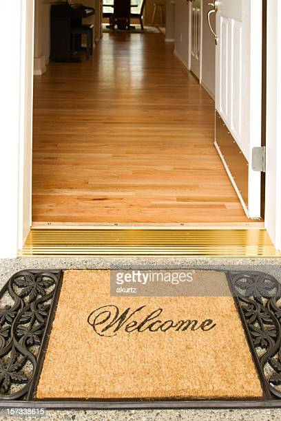 A welcome home mat placed outside of an open door
