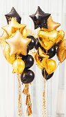 Welcome home party decoration. Golden and black round, heart, star shaped balloons on white background.