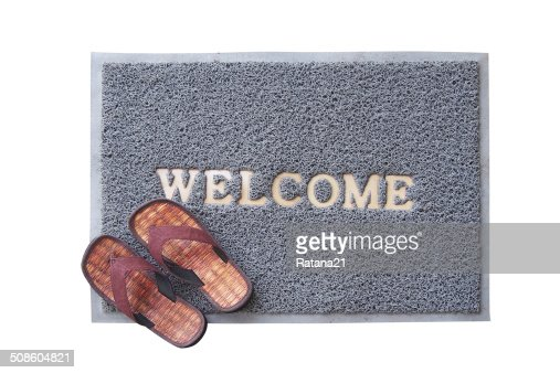 welcome mat with brown sandals on floor : Stock Photo