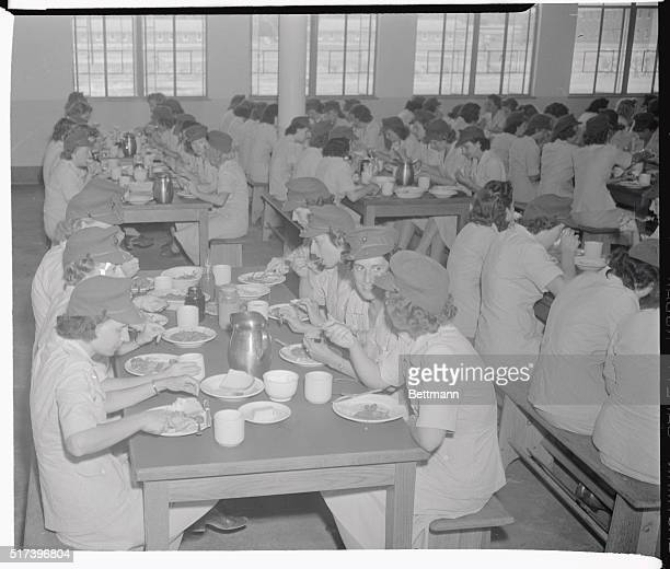A welcome sight at any military camp is the mess hall at chow time Here a group of women Marines is shown as they sit down to a meal in one of the...
