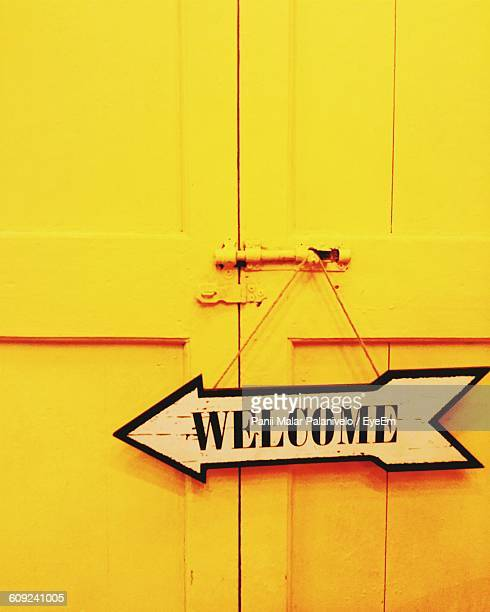Welcome Sign Hanging On Closed Yellow Door