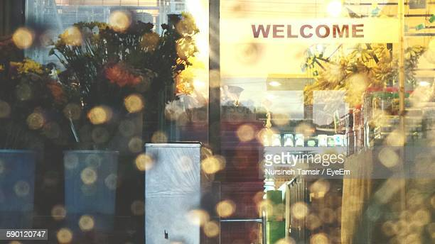 Welcome Sign On Shop Seen Through Car Window