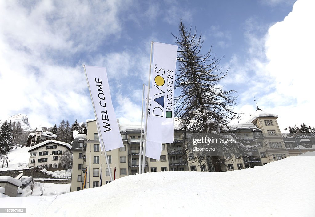 Welcome to Davos and Klosters flags sit planted in the snow in Davos, Switzerland, on Monday, Jan. 23, 2012. German Chancellor Angela Merkel will open this week's World Economic Forum in Davos, Switzerland, which will be attended by policy makers and business leaders including U.S. Treasury Secretary Timothy F. Geithner. Photographer: Chris Ratcliffe/Bloomberg via Getty Images