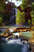 Blue-green water cascades down layers of rock at Havasu Falls in Arizona.