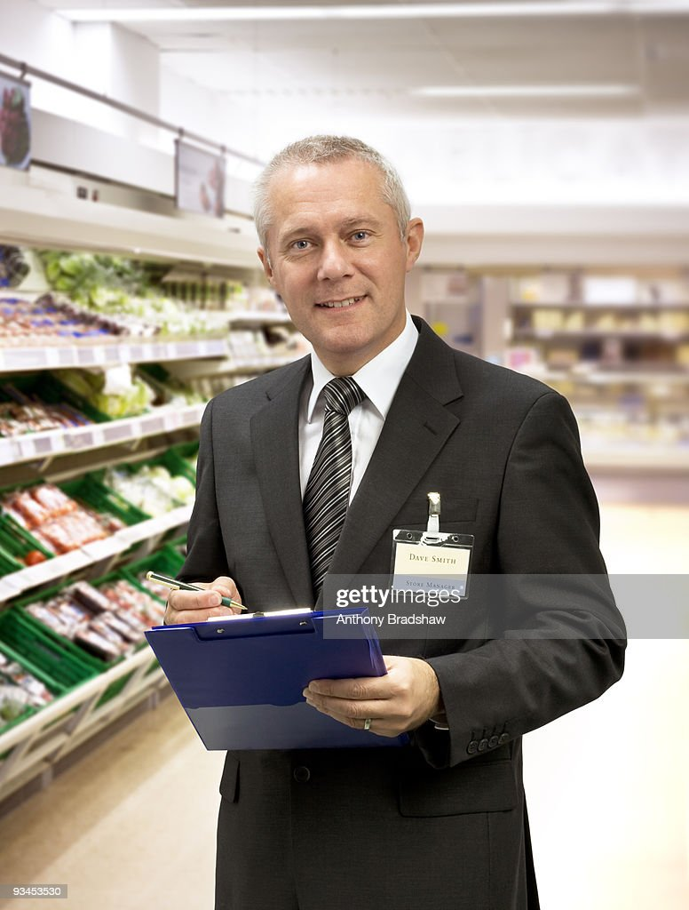 Welcoming supermarket manager : Stock Photo
