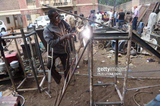 A welder and member of the Polio Victims Trust Association tries to weld a panel at the workshop in Kano northwest Nigeria on April 21 2017 The World...