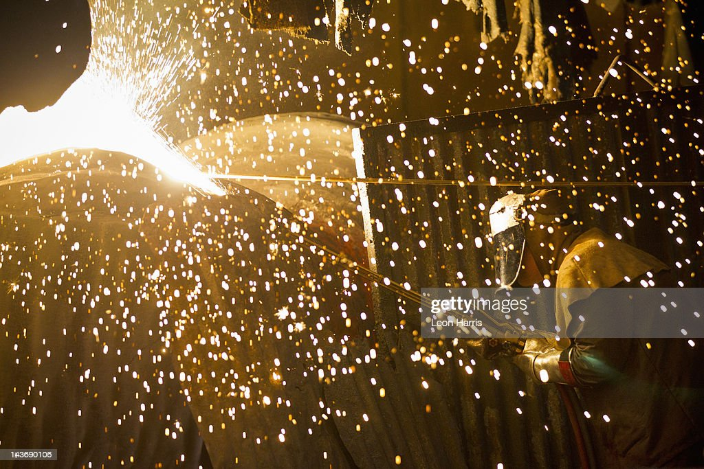 Welder at work in steel forge : Stock Photo