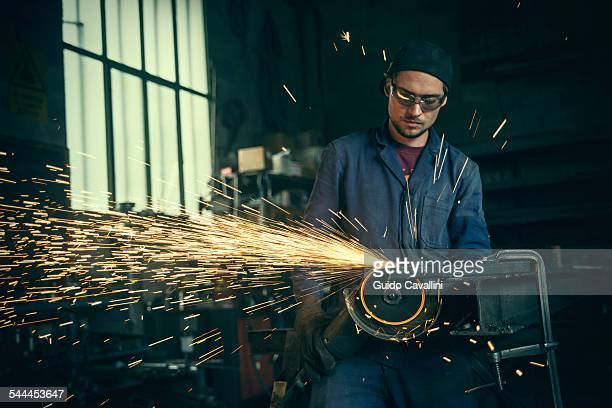 Welder cutting iron in workshop