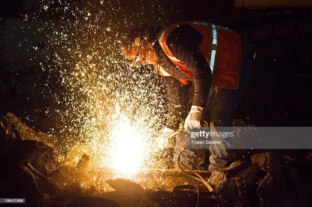 Welder cutting rail with oxy-acetylene torch
