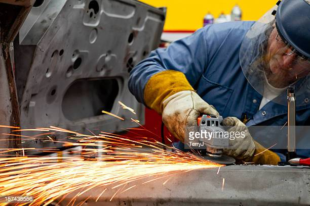 Welder Grinds a Support Piece after Welding in Place