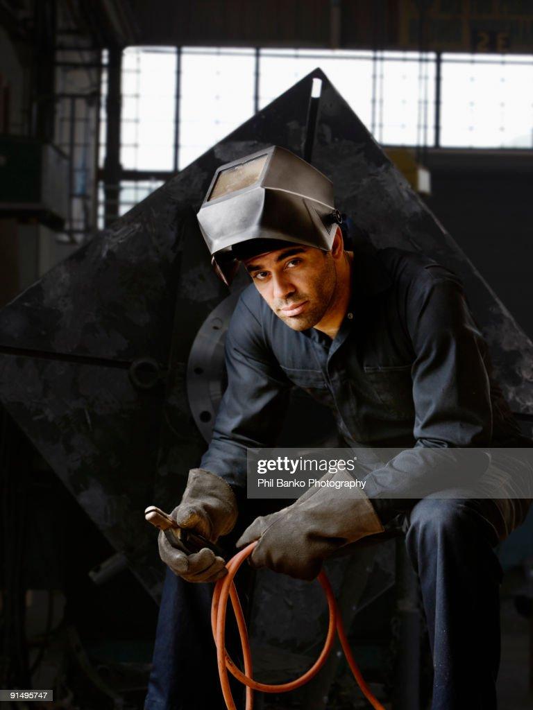 Welder in helmet and gloves in warehouse