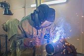 Welder in yellow gloves welds two pieces of steel pipe using electric welding in production. Arc welding workshop