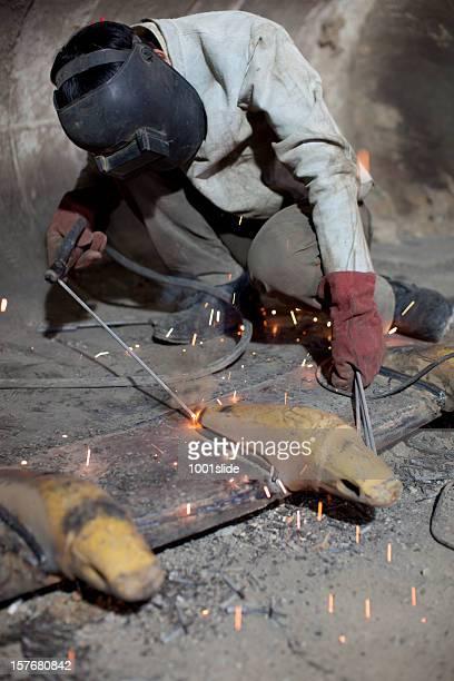 Soldador está muy ocupada con calefacción electrodo en cubo de cargador