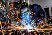 welder is welding assembly car parts in factory with protection mask