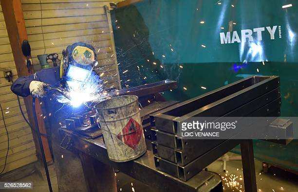 A welder of the Marty Sports company work on pieces of metal on April 27 2016 in SaintClementdelaPlace western France Marty Sports is the equipment...
