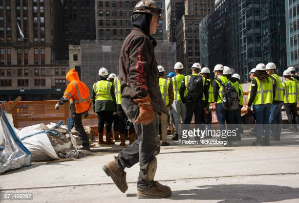 A welder on the One Vanderbilt skyscraper construction project walks past a group of visitors from a real estate company April 19 2017 in New York...