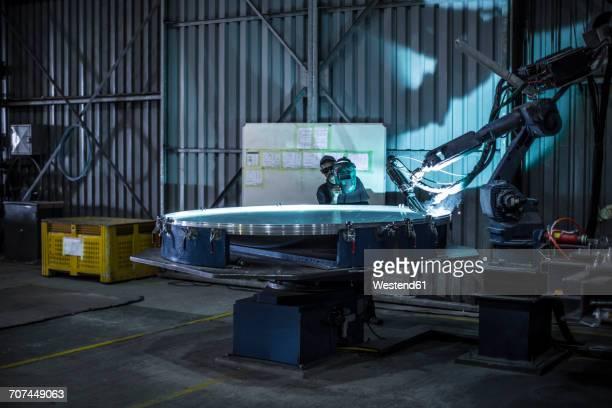 Welder standing behind industrial lathe cutting steel in factory