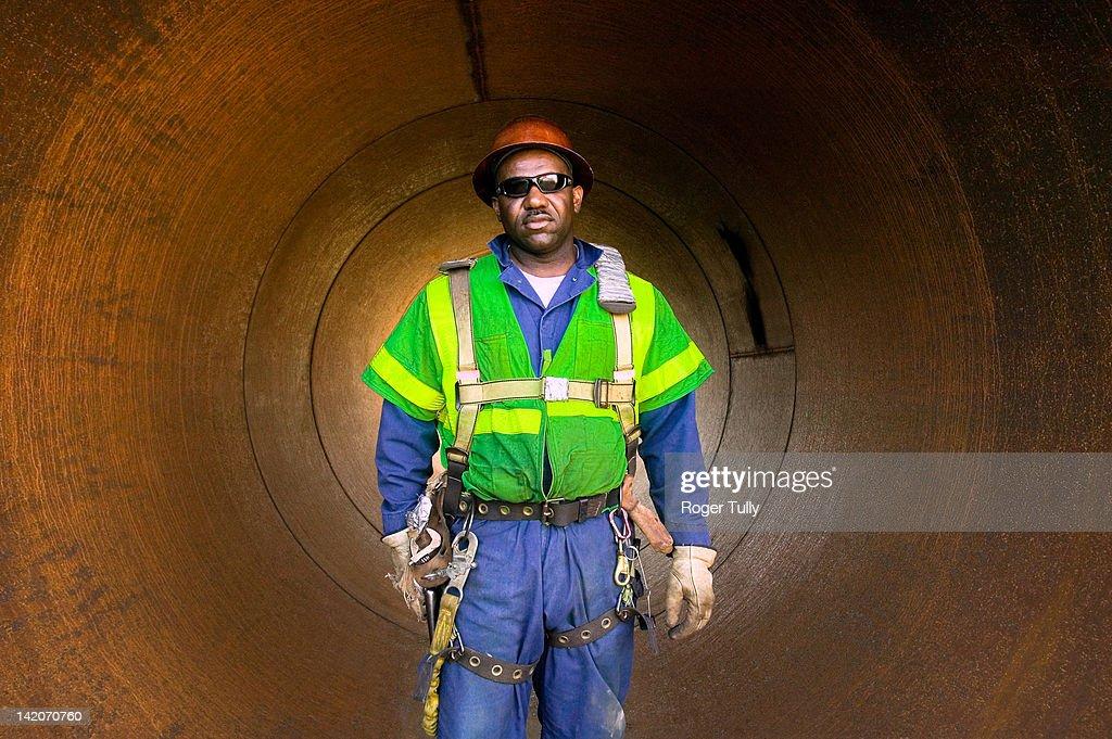 Welder standing in pipe : Stock Photo