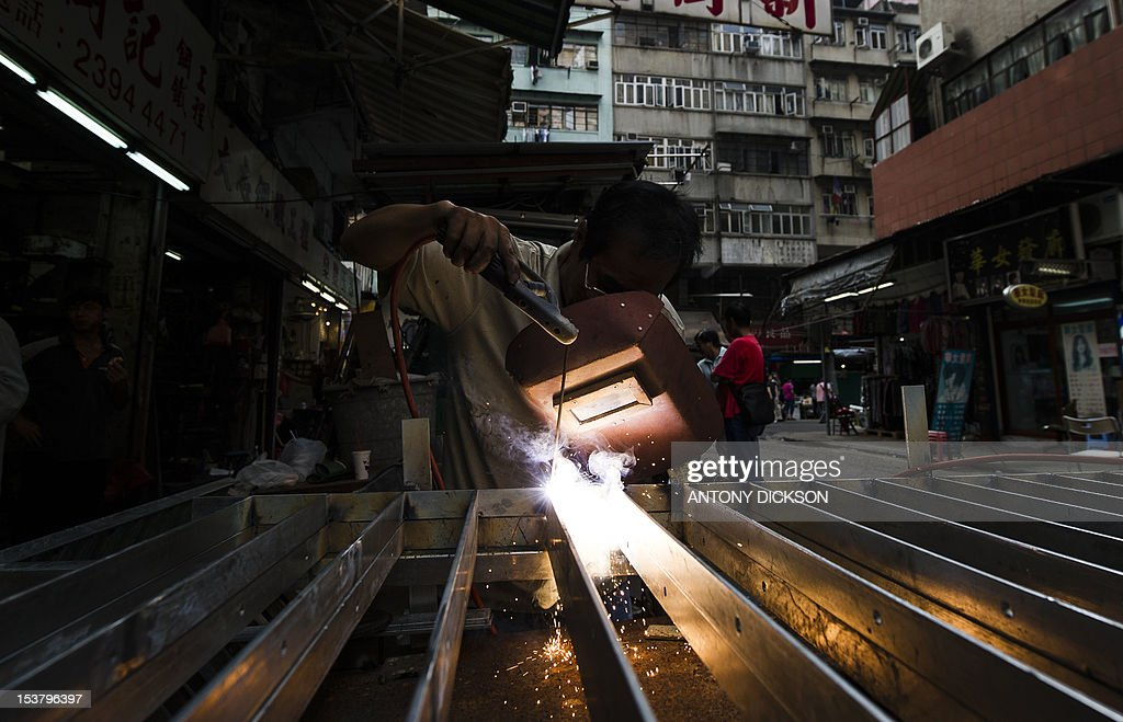 A welder strikes an arc as he produces a hand railing and fence out of galvanised steel in Hong Kong on October 9, 2012. The IMF cut its growth forecasts for developing Asia, blaming a slowdown in Europe and the US, and warned that China's attempts to boost its economy had not taken hold. AFP PHOTO / Antony DICKSON