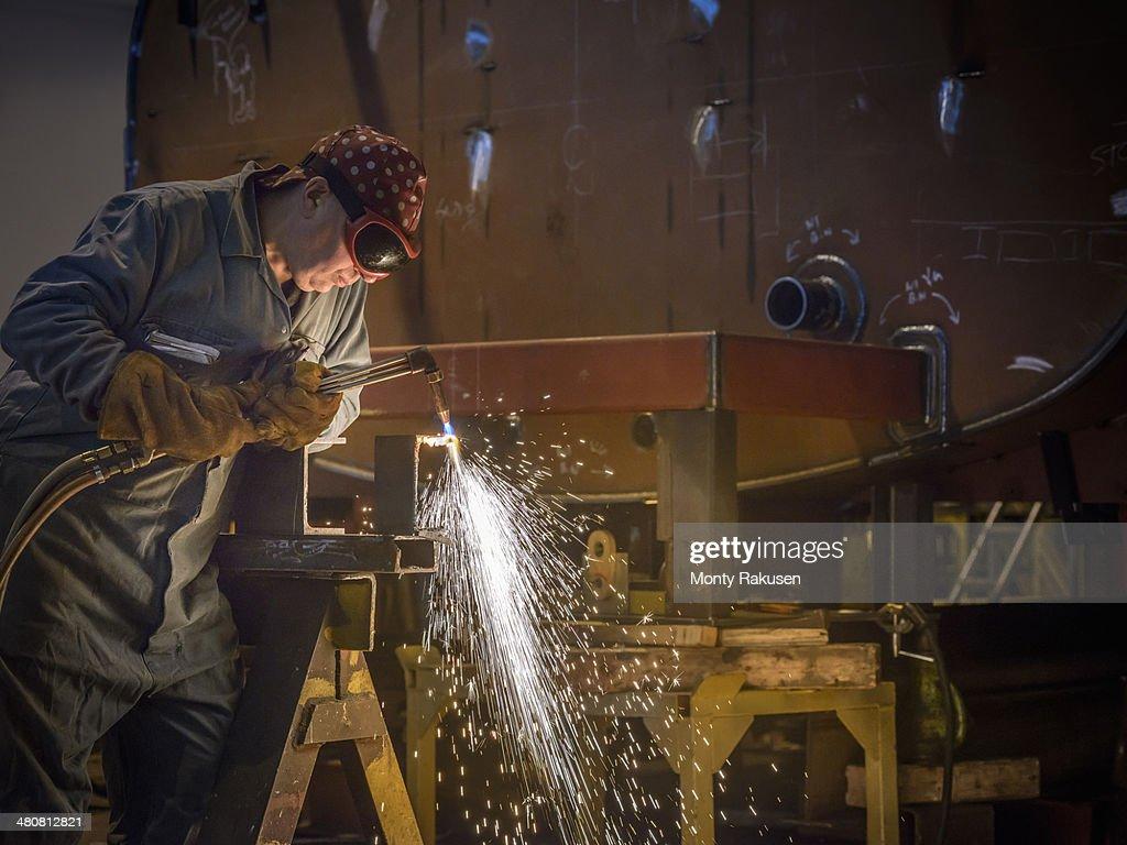 Welder using oxyacetylene torch to cut steel in factory