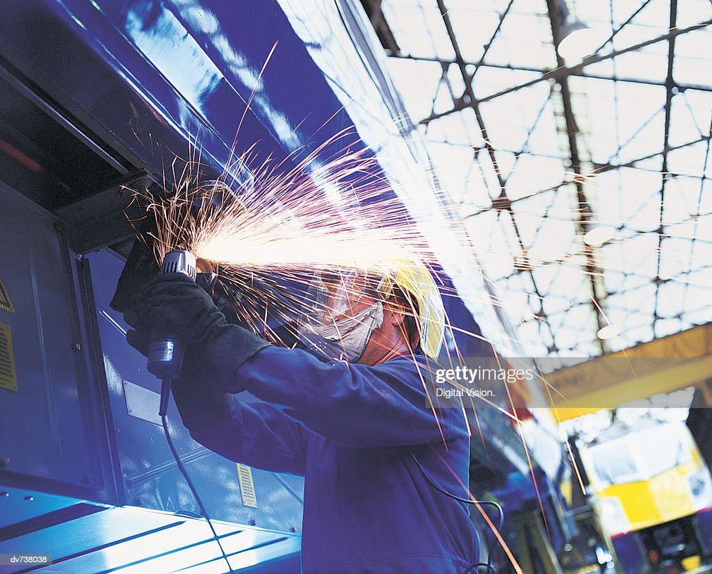 Welder Wearing Protective Clothing Working On Train in Factory