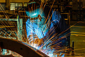 Worker, welding in a car factory with sparks, manufacturing, industry