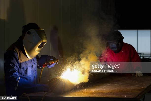 Welder with personal protective equipment and protective mask welding steel pipe in factory.