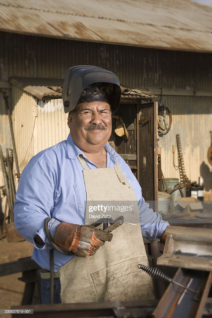 Welder with torch standing in work shop, smiling, portrait : Stock Photo